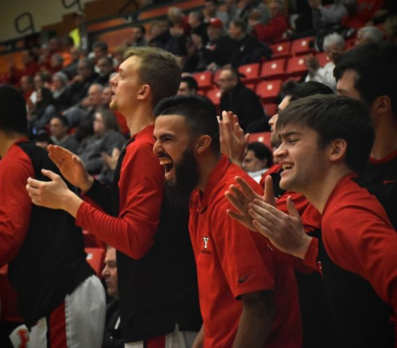 Tribune Chronicle / John Vargo  YSU senior point guard Francisco Santiago, center, is out for the season with an ACL tear to his right knee. Santiago cheers on his team during Thursday's win against Milwaukee. Teammates Jacob Brown, left, and John Kirinic, right, are also pictured.