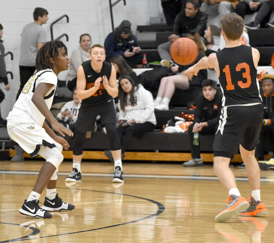 Tribune Chronicle / Joe Simon Howland's Connor Tamarkin (13) passes to teammate Frankie Manios, center, while being defended by Warren G. Harding's D'Muntize Owens on Tuesday at Warren G. Harding High School.