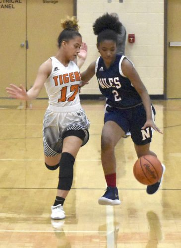 Tribune Chronicle / Marc Weems Anezah Fryer, right, of Niles dribbles against Howland's Ka'Rina Mallory Wednesday.