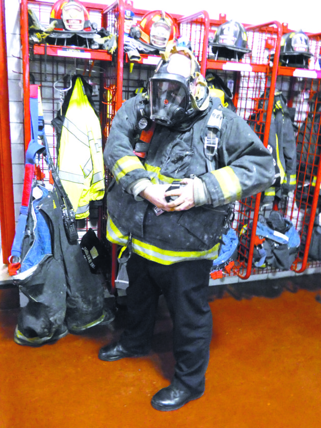 Tribune Chronicle / Jon Wysochanski Weathersfield fire Capt. Tom Lambert suits up in his turnout gear Friday. The department, along with several others, is seeking grant money to purchase equipment and gear aimed at preventing cancer in firefighters.