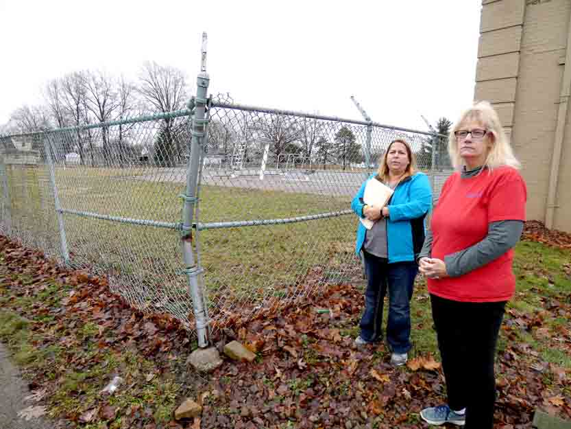 Tribune Chronicle / Jon Wysochanski Aimee Cantola, left, and Beth Nolen, members of the Niles Save the Pool Committee, stand outside the shuttered facility last week. The two have been working for more than a year to get the pool reopened. It was closed in 2014 because of the city's financial problems.