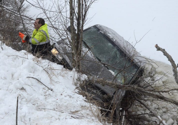 011618...R VEHICLE LAKE 1...Vienna...01-16-18...Mike Capito of Sorice Towing climbs the steep bank of Girard Lake along Niles-Vienna Rd. as the Chevy Astro van is pulled from the lake Tuesday morning by Sorice Towing...by R. Michael Semple