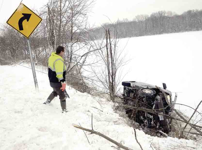 Tribune Chronicle / R. Michael Semple Mike Capito of Sorice Towing looks down the steep slope of Girard Lake along Niles Vienna Road in Vienna as a Chevy Astro van is pulled from the lake Tuesday morning. A Burghill woman and five young children were rescued by passers-by after the van slid off the road and partially crashed through the ice at the edge of the lake.