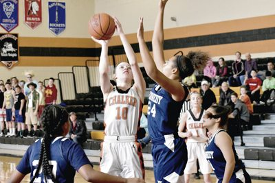 Tribune Chronicle / Marc Weems Chalker's Caitlyn Stuart (10)goes up for a shot over John F. Kennedy's Naomi Herman during their game Saturday in Southington. The Wildcats won the non-conference matchup, 49-41.
