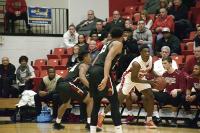 Tribune Chronicle / John Vargo IUPUI's Ron Patterson, foreground, and Nick Rogers, left, try to trap Youngstown State's Garrett Covington during Saturday's game in Youngstown. The Penguins won, 85-62.