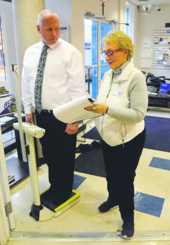 Jim Stitt, left, is weighed in Thursday by St. Joe's at the Mall manager Shirley Lisk  for the 17th annual Tribune Chronicle / Mercy Health Fitness Challenge.