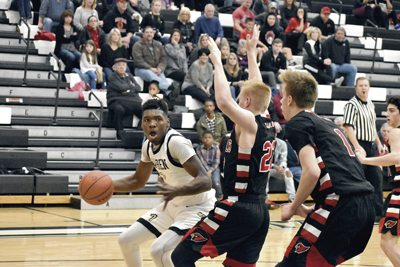 Tribune Chronicle / Marc Weems Warren G. Harding's Terrion Jackson, left, dribbles inside while being defended by Canfield's Ian McGraw, center, and Aydin Hanousek, right, during Saturday's 54-38 Raiders victory in Warren.