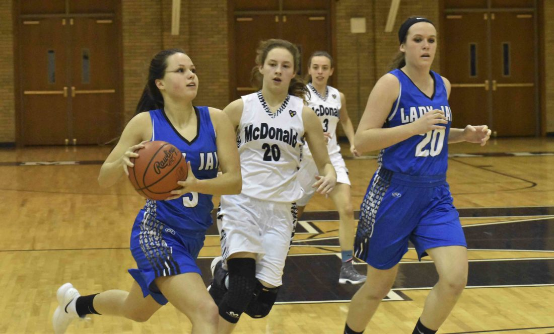 Tribune Chronicle / Marc Weems Jackson-Milton's Emily Williams, left, drives as McDonald's Molly Howard, center, and Jackson-Milton's Ashley Cameron trail the play during Monday's game at McDonald High School. The Blue Devils won, 37-32.