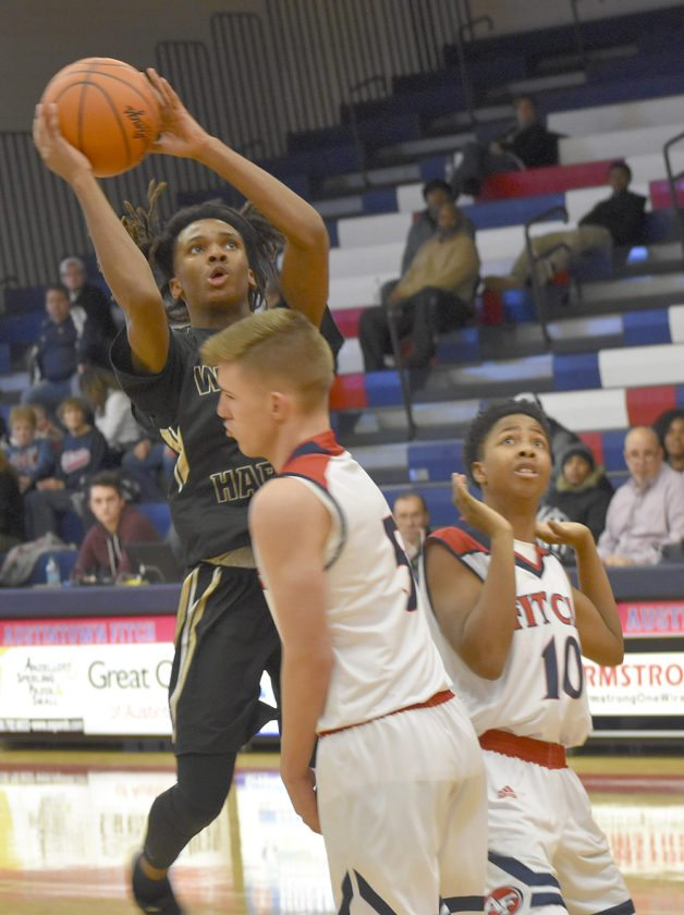 Tribune Chronicle / Joe Simon Warren G. Harding's D'Muntize Owens goes for a lay-up while being guarded by Fitch's Cole Constance, left, and Chris Brown, right. The Falcons won the game, 50-44.
