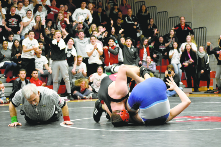 Tribune Chronicle / Joe Simon Canfield's crowd celebrates as the Cardinals' David Crawford finishes a pin of Louisville's Lathan Larsen on Wednesday at Canfield HighSchool. Canfield won the match, 33-31, to advance to the state quarterfinals in Columbus on Feb. 11.