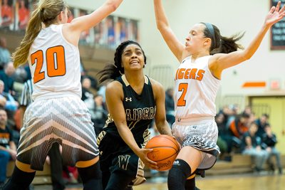 Special to Tribune Chronicle / Dianna Oatridge Brayleonna Woods of Warren G. Harding splits two Howland defenders on the way to the basket Wednesday night.