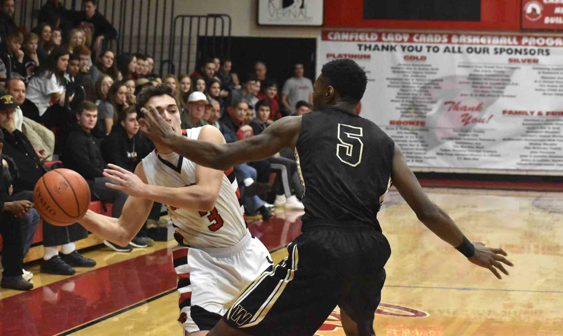 Tribune Chronicle / Marc Weems Warren G. Harding's Delmar Moore defends against Canfield's Ben Shapiro during Friday's game at Canfield High School. The Raiders swept the season series from the Cardinals and won, 62-43, on Friday.