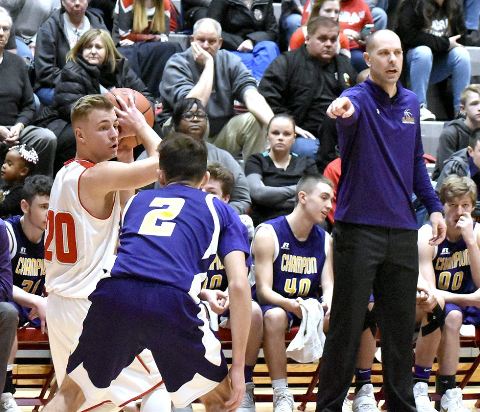 Tribune Chronicle / Marc Weems Champion coach Nathan Kish, right, instructs his players as the Flashes' Chase Wheelock (2) guards Benton Tennant of LaBrae Tuesday night. The Vikings beat Champion, 60-55, to clinch the All-American Conference Blue Tier.