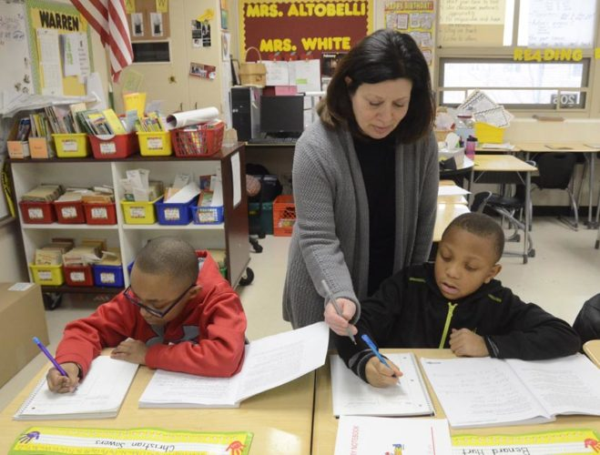 Tribune Chronicle / R. Michael Semple Lincoln third-grade teacher Mary Jo Altobelli, center, works with Ben Hurt, 8, right and Christian Sowers, 8, left, on their reading skills. The percentage of Warren's third-grade students whose reading levels are high enough to promote them to fourth grade has been increasing.