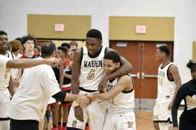 Tribune Chronicle / Joe Simon Warren G. Harding's Delmar Moore, left, and Trivell Trimble, right, celebrate the Raiders' 61-60 victory over Canton McKinley on Tuesday at Warren G. Harding High School.