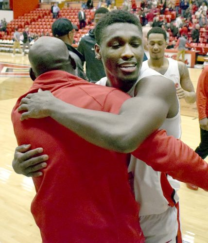 Tribune Chronicle / John Vargo Youngstown State freshman Garrett Covington gets a hug from his father, John Covington, Wednesday night at the Beeghly Center after the younger Covington sank a game-winning shot in the Penguins' 75-73 victory over Oakland.