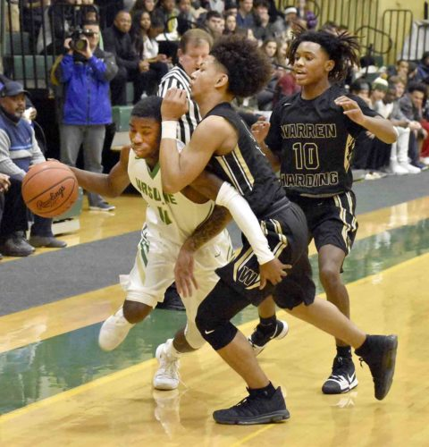 Tribune Chronicle / Marc Weems Warren G. Harding's Chris Hughes, center, and D'Muntize Owens (10) pressure Ursuline's RJ Clark into a turnover Friday during the Raiders' 65-53 win at Ursuline.