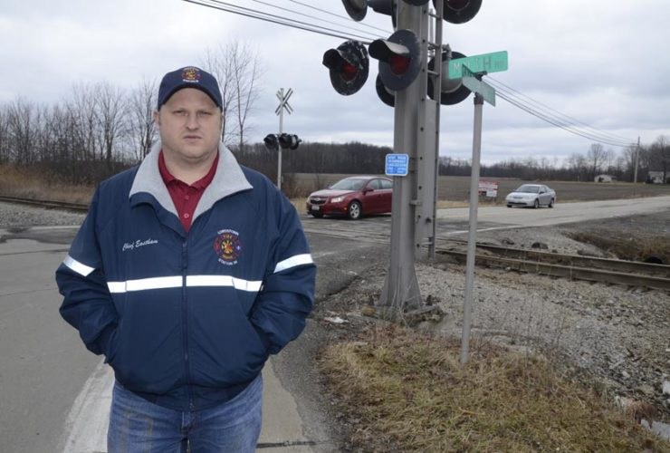 Tribune Chronicle / R. Michael Semple Lordstown fire Chief Travis Eastham stands at the intersection of Muth and Salt Springs roads in the village near the CSX railroad crossing. Vehicles on the roadways often have to wait for a period of time at the crossing while train cars stop to load and unload cargo. The General Motors complex is nearby. Village officials are exploring construction of a bridge over the tracks to ease safety and traffic concerns.