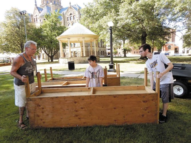 From left, George Rutherford of Niles, Dominic Bowser of Warren and Jeremy Sidoti of Warren, move benches around Courthouse Square in downtown Warren to prepare for the 2017 Italian-American Festival. The committee that oversees the annual festival is mulling over a move to the Eastwood Mall in Niles. Tribune Chronicle / Bob Coupland