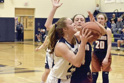 Tribune Chronicle / Marc Weems Brookfield's Bailey Drapola, left, goes in for a shot while being guarded by Howland's Kendyl Buckley, center, in the first half of their game Monday in Brookfield. Howland's Alex Ochman (20) looks on during the Tigers' 61-26 victory.