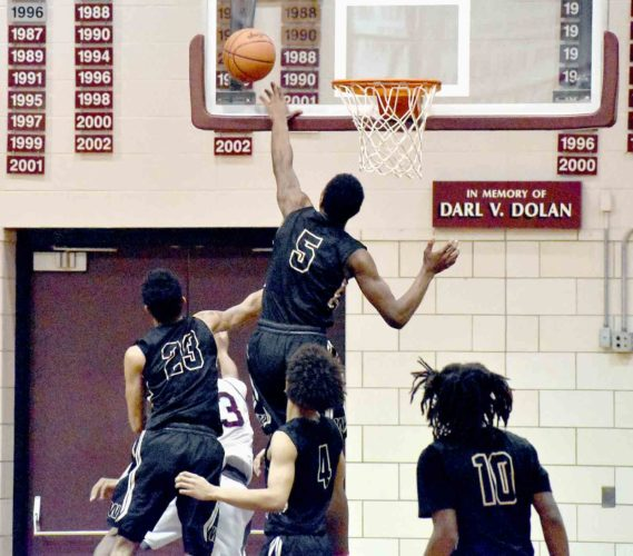 Tribune Chronicle / Marc Weems Warren G. Harding's Delmar Moore blocks a Boardman shot as teammates Dom McGhee (23), Chris Hughes (4) and D'Muntize Owens (10) look on.