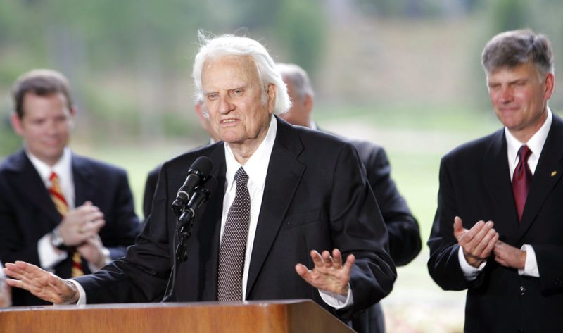 FILE - In this May 31, 2007 file photo, Billy Graham speaks as his son Franklin Graham, right, listens during a dedication ceremony for the Billy Graham Library in Charlotte, N.C..  Graham, who transformed American religious life through his preaching and activism, becoming a counselor to presidents and the most widely heard Christian evangelist in history, has died. Spokesman Mark DeMoss says Graham, who long suffered from cancer, pneumonia and other ailments, died at his home in North Carolina on Wednesday, Feb. 21, 2018. He was 99.(AP Photo/Gerry Broome)