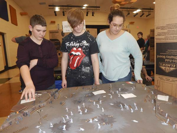 Eighth graders Tim Herdman, 13, left, Niko Zerefos, 14, and Audrionna Taylor, 14, of Southington, show their History Day project on Battle of Verdu.