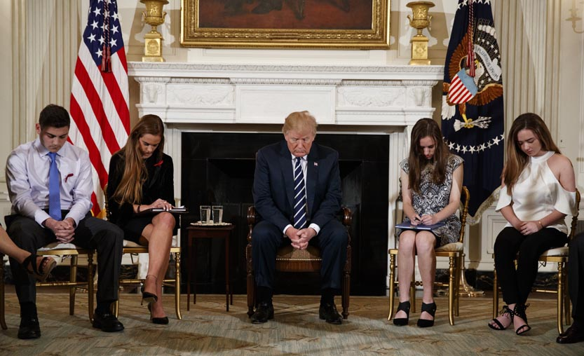 AP From left, Marjory Stoneman Douglas High School student Jonathan Blank, Julia Cordover, the student body president at Marjory Stoneman Douglas High School, President Donald Trump and Marjory Stoneman Douglas High School students Carson Abt and Ariana Klein bow their heads during the opening prayer before a listening session with high school students, teachers, and others in the State Dining Room of the White House in Washington Wednesday.