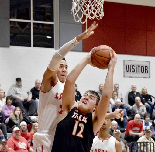 Tribune Chronicle / Marc Weems LaBrae's Tyler Stephens, left, is about to block a shot by Shane Eynon of Springfield on Friday at LaBrae. The Vikings ended the regular season 21-1 with a 74-57 victory.