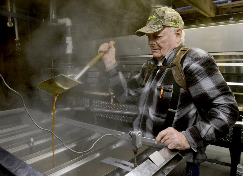 Tribune Chronicle / R. Michael Semple With steam rising from the finisher, Dick Sutton of Kinsman checks the syrup during the process of boiling sap down to make maple syrup. Sutton is one of about 900 maple syrup producers in Ohio.