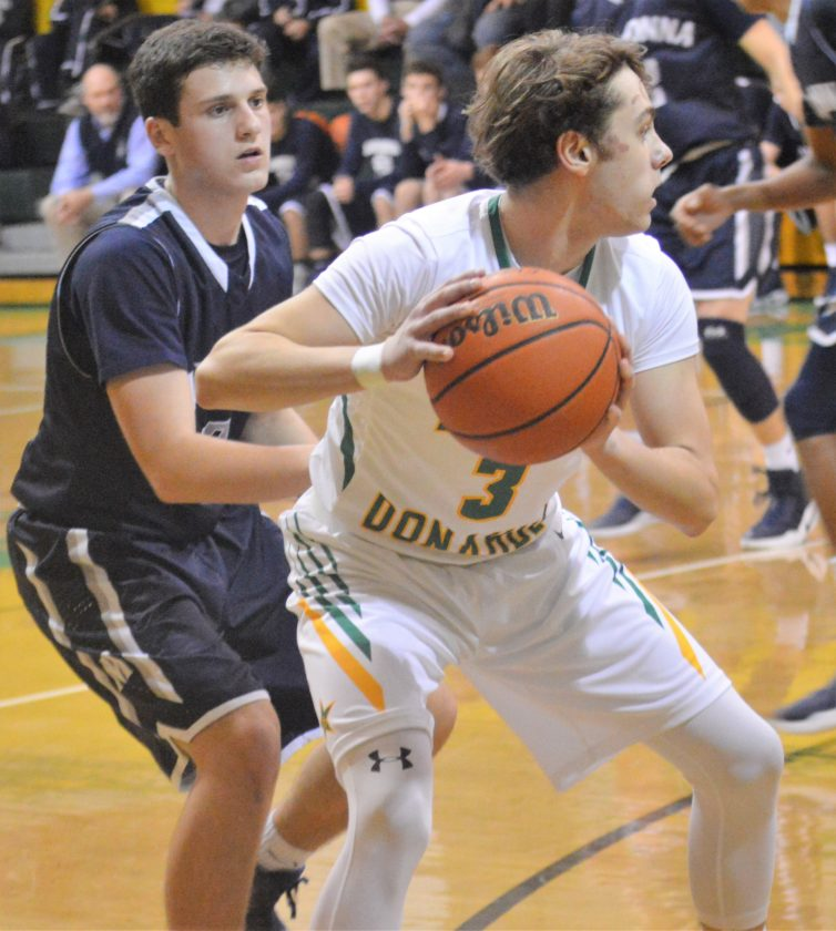JUMPER — Weirton Madonna senior Jimmy Mazzone plays defense against Bishop Donahue's Logan Ruckh during Tuesday's game in McMechen. The Blue Dons won, 65-61. (Cody Tomer)