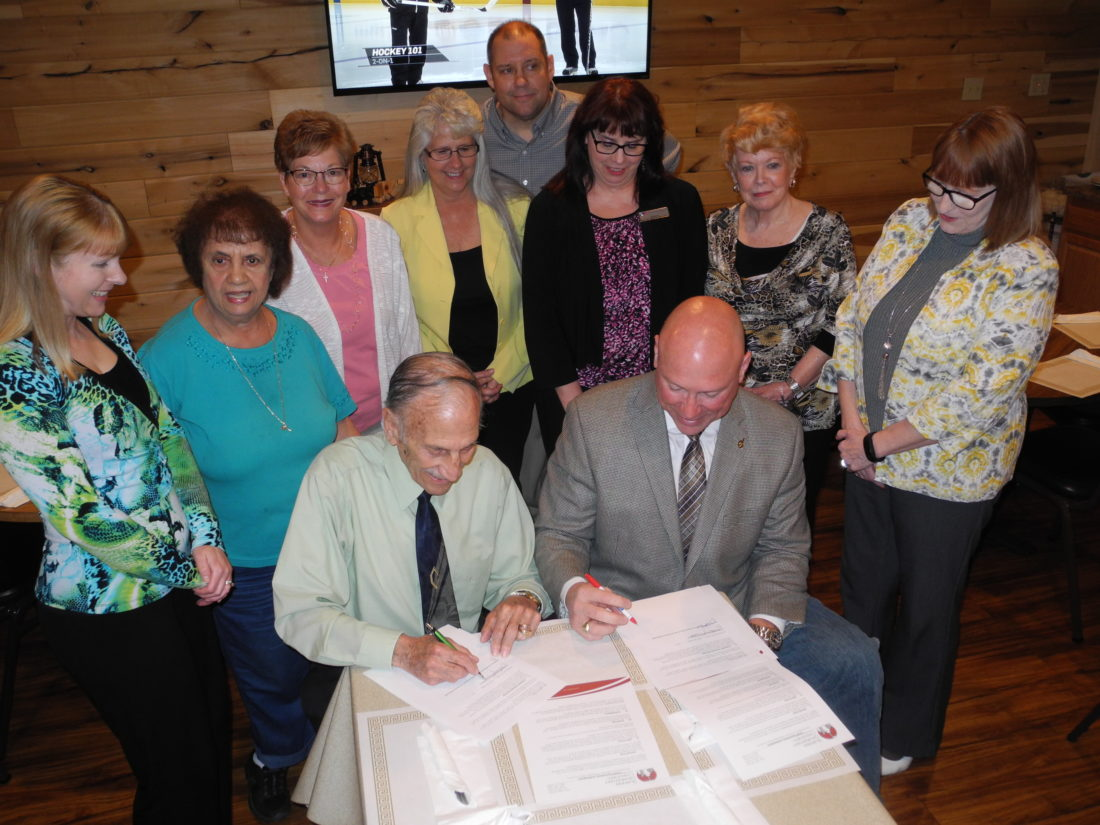 "PARTNERSHIP FORMED — Members of the Follansbee Chamber of Commerce watch as Chamber President Tony Paesano, seated left, signs agreements with Pat Ford, executive director of the Business Development of the Northern Panhandle; calling for the chamber to serve as its task force for economic development in the city and a Good Neighbor Agreement involving the former Follansbee Steel property owned by the economic development group. Behind Paesano and Ford are, from left, Brandy Puskarich, Carmel Esposito, Charlotte Kolenc, Olive McGee, Vito ""Skip"" Cutrone, Alexis Pace, Pat Accettolo and Debbie Puskarich. -- Warren Scott"