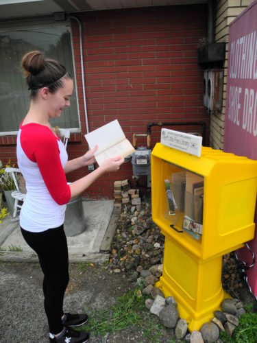Rene Hutchison of Hooverson Heights checks out a book from the new Little Free Library posed in her community by the Brooke County Public Library. — Warren Scott