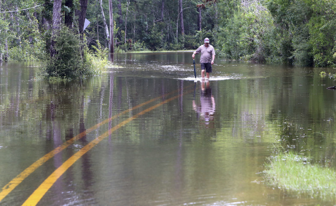 Britt Singletary walks down Brandon James Drive to his car parked outside the Wells Ferry Landing subdivision in Biloxi, Miss., on Friday. Rivers across South Mississippi are above flood stage after several days of heavy rain from Tropical Storm Cindy. -- Associated Press