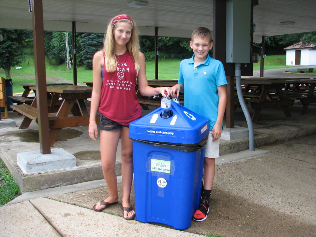 RECYCLING — Nadia Lysle of Hammondsville and Ethan Wolf of Zanesville recycled their water bottles at a new recycling container at Stratton Park. -- Contributed