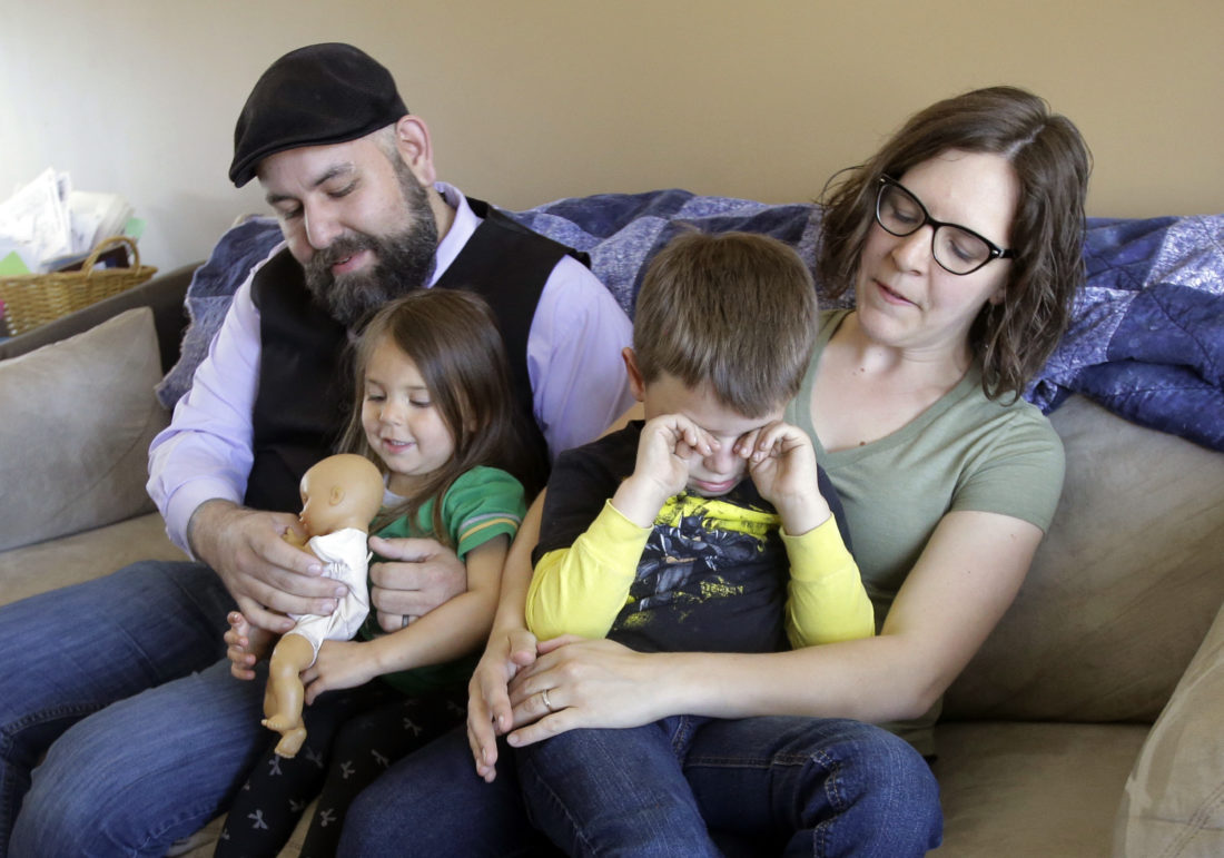 "WORRIED — In this May 4 file photo, Jake Martinez, who has epilepsy, holds his daughter Jenny, while his wife Kat, holds their son Joe, at their home in Murray, Utah. While Republicans in Congress failed this week to craft a new health care plan, they did succeed in shaking the confidence of those who rely on the act the most. Martinez said Obamacare made it possible to get affordable coverage for himself, his wife and their children. Without it, he may decide to drop out of college so he can afford insurance. ""If I can't treat my epilepsy, I can't drive, I can't go to work. Things that are day-to-day activities become health hazards,"" Martinez said. -- Associated Press"