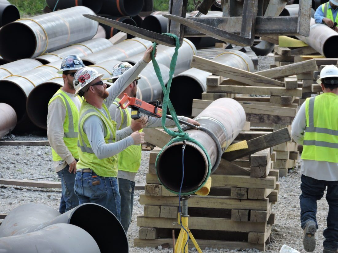 WORK CONTINUES — Natural gas industry workers load pipe onto a truck before going to a construction site in the Upper Ohio Valley. -- File photo