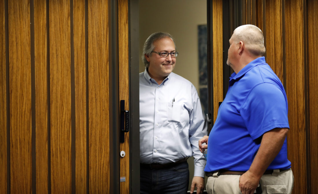 """In this Aug. 2, photo, U.S. Rep. David Young, R-Iowa, speaks with a resident during a stop at the Glenwood City Hall, in Glenwood, Iowa. Conservatives in Young's district are angry with the GOP's failure to repeal and replace Obamacare. Independents don't like the partisan approach. And now Democrats are making an issue of Young's vote for a health care bill that President Donald Trump called """"mean."""" -- Associated Press"""