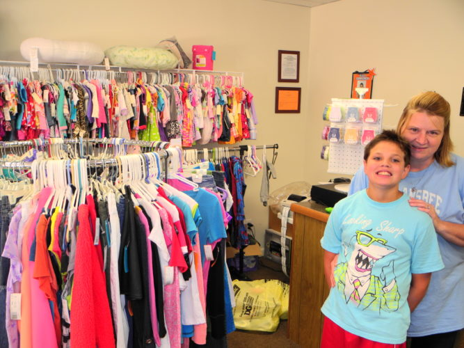 CONSIGNMENT SHOP — Barb Beatty, owner of Lollipops and Gumdrops, enjoys a moment with her son, Sidney, at her new consignment store at 59 Town Square in Wellsburg. The shop offers an assortment of gently used children's, junior girls and maternity clothes. -- Warren Scott