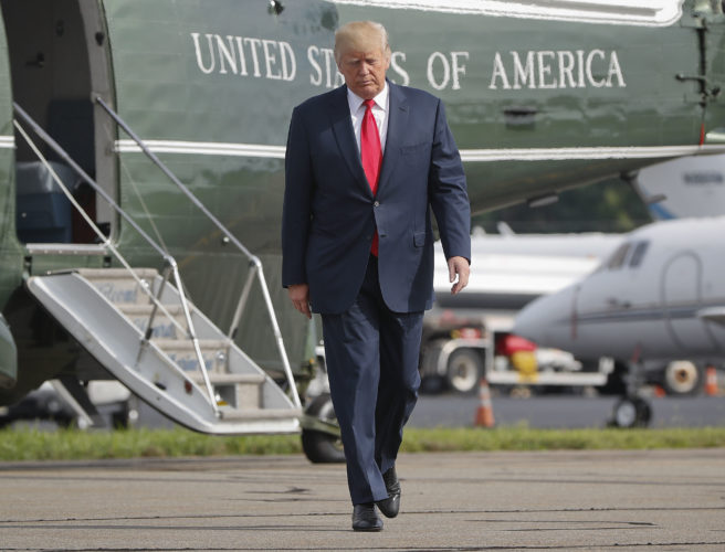 In this Aug. 14, file photo, President Donald Trump walks across the tarmac from Marine One to board Air Force One at Morristown Municipal Airport in Morristown, N.J. on Monday. Bombarded by continued attacks from fellow Republicans, Trump on Thursday, dug into his defense of racist groups by attacking members of his own party and renouncing the rising movement to pull down monuments to Confederate icons. -- Associated Press