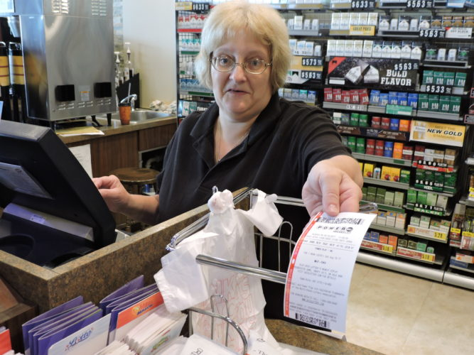 IS IT A WINNER? — Stacie Travis, a cashier at the Convent Food Mart on Sunset Boulevard, hands a single Powerball ticket to a customer Friday morning. The Powerball jackpot prize was at $535 million Friday afternoon and still growing in advance of tonight's drawing at 11 p.m. -- Dave Gossett