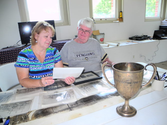 Beech Bottom Mayor Becky Uhlly and Councilman Ted Westfall study some old photos related to the Windsor Power Plant, which began operations on Aug. 19, 1917. Also before them is a trophy bearing the records of the plant's adult baseball teams in 1924 and 1925. Village officials are working with a group of volunteers to mark the plant's anniversary while also celebrating its own 100th anniversary with a community picnic on Sept. 2 and the 100th anniversary of an airfield near the village — home to the West Virginia Flying Corps — on Sept. 30. -- Warren Scott