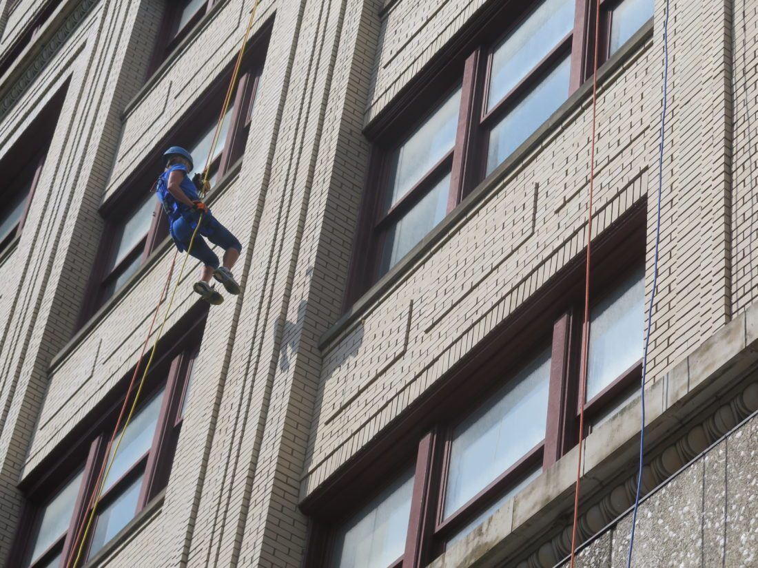 SPECIAL FUNDRAISER — Sara Quigley floats toward the ground across the surface of the Stone Center using rappelling equipment on Saturday. She was one of many participants in the YWCA's Over the Edge fundraiser. -- Alec Berry