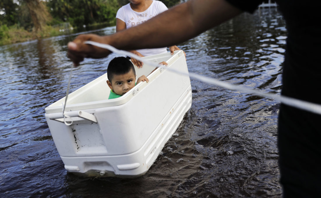 GOING DOWN THE STREET — Alfonso Jose Jr., 2, is floated down his flooded street by his parents as they wade through water to reach an open convenience store in the wake of Hurricane Irma in Bonita Springs, Fla., Tuesday. -- Associated Press