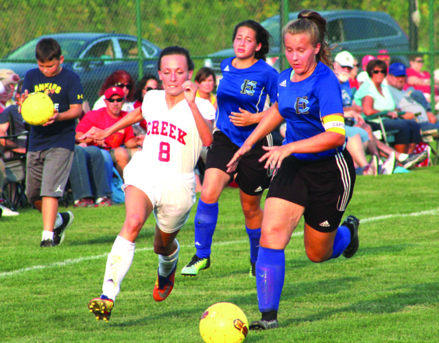 TOO FAST — Indian Creek's Kelsey Lewis runs with the ball past Harrison Central's Juliana Rose (front) and Jenna Easlick on Monday. Lewis finished with a goal and two assists in Indian Creek's 5-2 victory. (Photo by Joe Catullo)