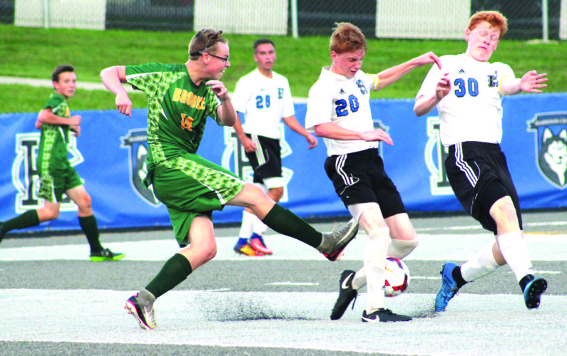 THROUGH THE LEGS — Brooke's Domenic D'Ulisse kicks the ball past Harrison Central's Dylan Redish (20) and Lucas Puskarich (30) while Corey Dunlap (28) watches on Tuesday. (Photo by Joe Catullo)
