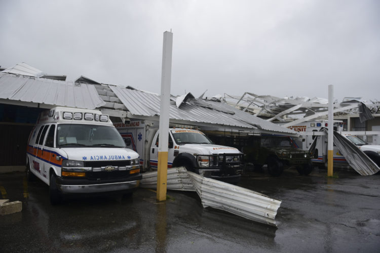 TRAPPED — Rescue vehicles from the Emergency Management Agency stand trapped under an awning during the impact of Hurricane Maria, which hit the eastern region of the island, in Humacao, Puerto Rico, Wednesday. The U.S. National Hurricane Center says Maria has lost its major hurricane status, after raking Puerto Rico. But forecasters say some strengthening is in the forecast and Maria could again become a major hurricane today. -- Associated Press