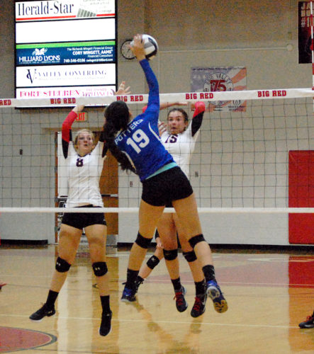 BLOCKING — Big Red's Suzie Rososchi (8) and Sidney Snyder (15) attempt to block an attack by East Liverpool's Mariah Peachey (photo by Andrew Grimm).