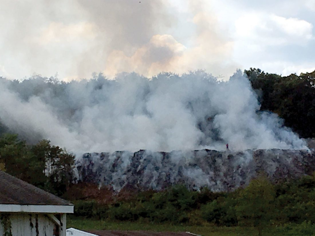 SMOKING HILLSIDE — This view from Race Track Road in Newell shows a billow of smoke as crews from a dozen area fire departments worked to extinguished a fire on a hillside on Trotter Drive Thursday afternoon. -- Steve Rappach