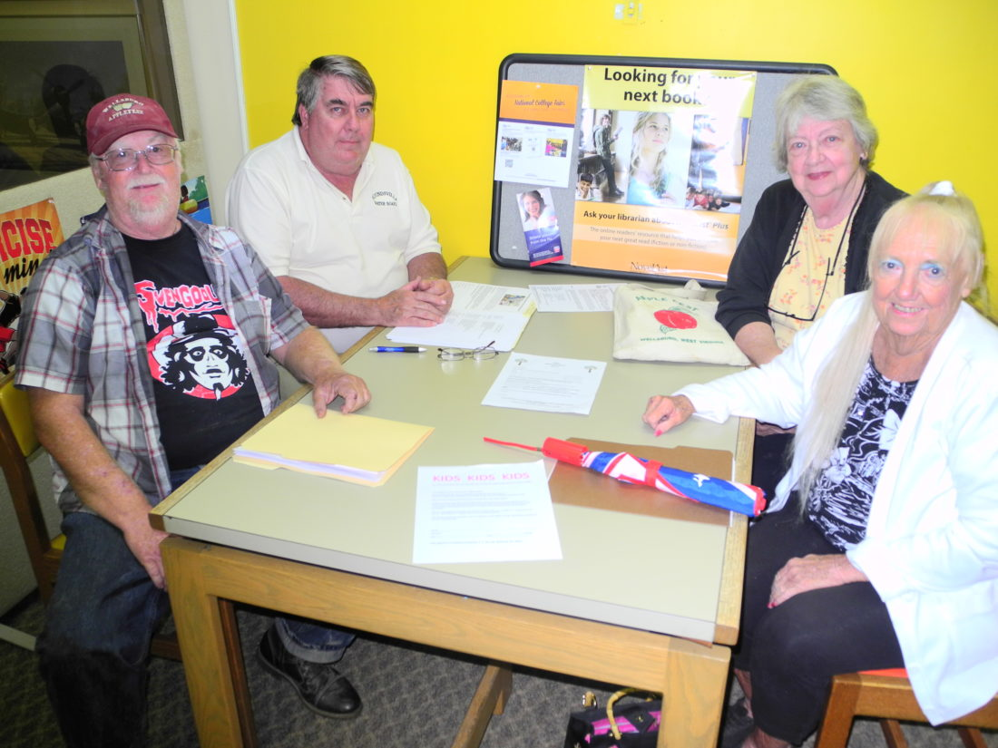 FESTIVAL PLANNED — Wellsburg Applefest Committee members, clockwise from left, Jerry Fluharty, Ernie Jack and Rita Ramsey, co-chairs; and Shirley Rogers prepare for the festival's 39th year, which will include booths for young entrepreneurs and artists and musical entertainment new to the festival as well as a variety of food and other vendors, amusement rides and other activities. -- Warren Scott